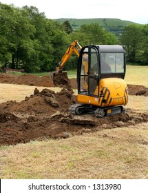 Man operating a mini digger in a field.