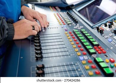 Man operating sound levels on audio mixer