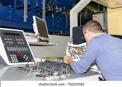 Man operator working on printing machine in print factory