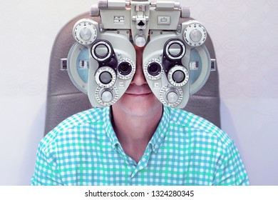 Man ophthalmologist examining patient man with optometrist trial frame. Male patient to check vision in ophthalmological clinic