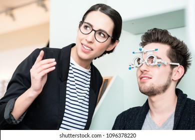 Man with optician at eyesight test for glasses in optician shop