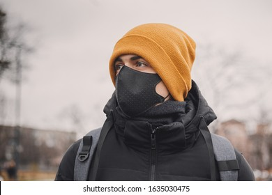 Man in orange hat takes off black medical mask on the street. Coronavirus is a virus that is endemic in China. Protection from the illness for children. Health safety concept