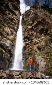 Man with orange jacket standing on one of the waterfalls Finsterbach in Sattendorf near lake Ossiacher See in Carinthia, Austria