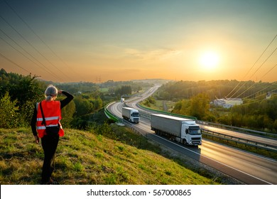 The man in the orange safety vest watching white trucks driving on a highway in the landscape at sunset. View from above.