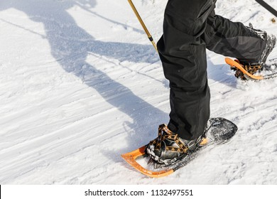 Man with orange snowshoe on the snow path. Man in snowshoes with trekking poles is the snow in the mountains. Snowshoe is most versatile and highest-performing backcountry shoe