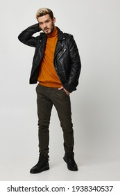 a man in an orange sweater and a leather jacket holds his hand in his pocket puzzled look model