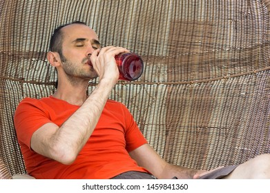 Man with orange t-shirt drinking alcohol straight from the bottle. Alcoholism concept.