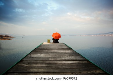 The man with the orange umbrella is sitting on a fishing pier, thinks, and he's looking at the blue lake