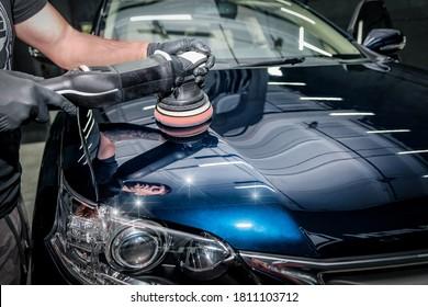 Man with orbital polisher in repair shop polishing car. Car detailing