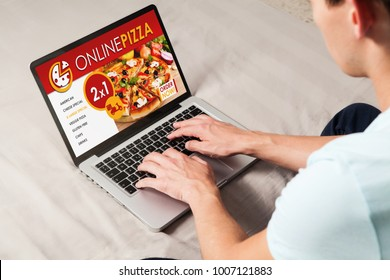 Man ordering pizza by internet with a laptop computer, sitting on the bed at home.
