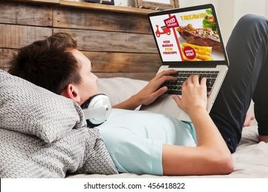 Man, der Essen im Internet bestellt, nimmt mit einem Laptop zu Hause Platz.