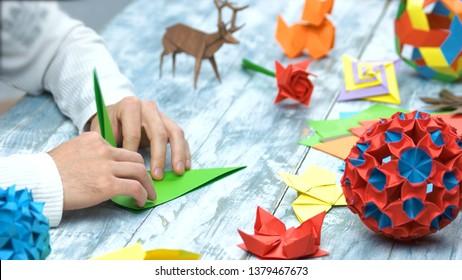 Mann am Origami-Faltenunterricht. Sammlung von schönen Origami-Figuren auf Holztisch. Traditionelles Origami-Papierfalten.