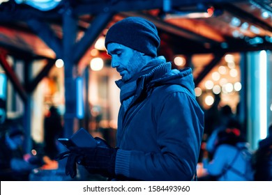 man outdoor in the city using a mobile phone - stylish freelancer in the winter season