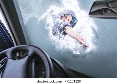 Man outdoor cleaning snow on his car windshield.View from inside of car.