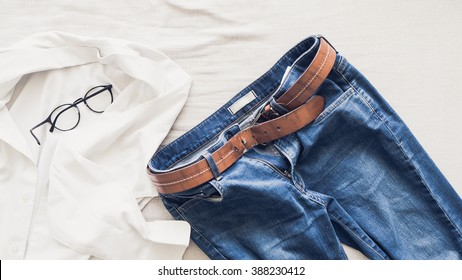 Man outfit laid on bed in the morning light with white shirt.