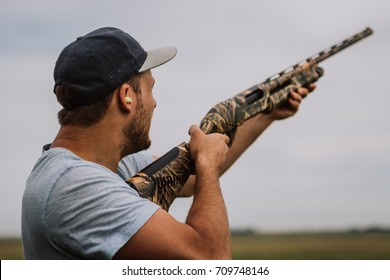 Man outside skeet shooting with his camo shotgun.