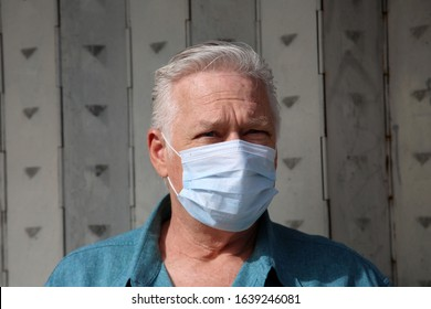A man outside wears a Paper Face Mask to keep safe from Dust, Smog, Virus's, and other harmful air born contaminants. Coronavirus and other flu's are spreading fear and sickness world wide. Caution.