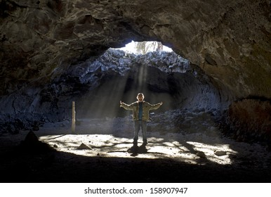 Man with outstretched arms standing in sunbeams shinning down through skylight in cave