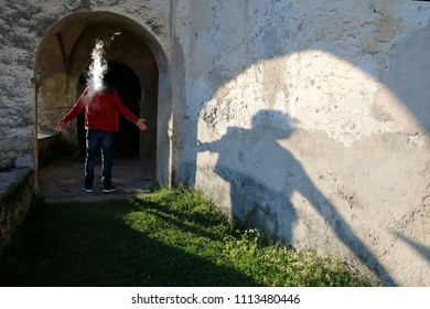 Man with outstretched arms is wrapped in smoke from a cigarette, shadow falls on a wall