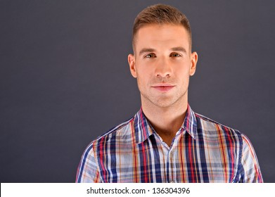 Man over dark background in squared shirt