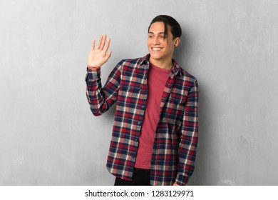 Man over grunge wall saluting with hand with happy expression