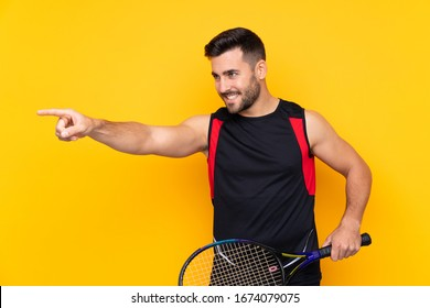 Man over isolated yellow background playing tennis