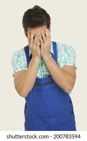 Man in overall covering face with hands
