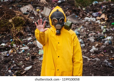 Man in overalls and gas mask shows a gesture to stop. In  background garbage dump. Concept of human pollution