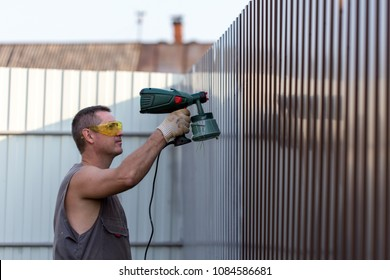 Man in overalls and protective glasses with spray gun in hand. Painting of metal fence