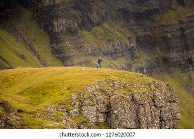 Man overlooking view Old Man of Storr in Autumn on the Isle of Skye, Scotland, UK.