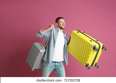 Man with overweight luggage on colorful background