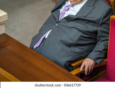 man with overweight. symbolic photo for beer belly, unsuccessful dieting and eating the wrong foods. Weight loss concept. Tight shirt. a man in a suit and tie is sitting in the chair