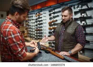 Man with owner choosing handgun in gun shop