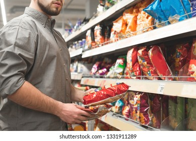 Man with a pack of chips in his hands in the supermarket snack department. Buyer selects and buys chips . Man chooses products in a grocery store.