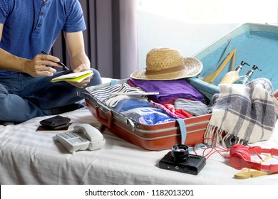 man   packing the luggage prepare for their journey trip with a lot of her cloth, he note and call check