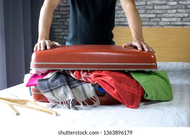 man   packing the luggage prepare for their journey trip with a lot of  their cloth, he use power to close the bag