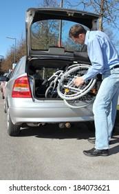 Man packing a wheelchair in a car's trunk