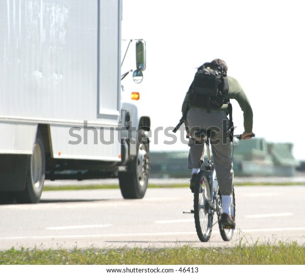a man with a packsack rides a bike on the roadway