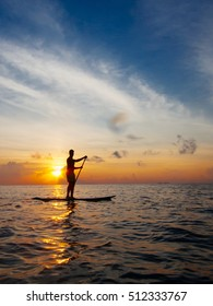 Man paddle boarding during a beautiful sunrise in Mexico