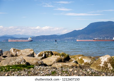 A man paddleboarding near Locarno Beach, Vancouver, Canada.