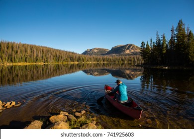 man paddles a canoe into a crystal clear mountain lake