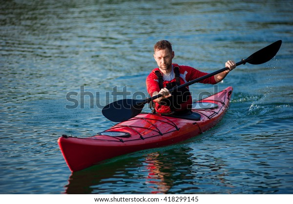 man paddles a red kayak on the pond near the shore, kayaking