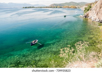 Man paddling in boat in calm Lake Ohrid, Macedonia