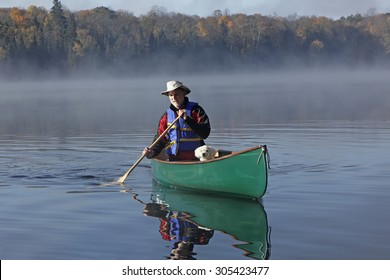 Man Paddling a Canoe on a Lake in Autumn with a Small White Dog in the Bow - Ontario, Canada
