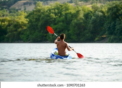 Man Paddling Kayak on the Beautiful River or Lake at the Evening