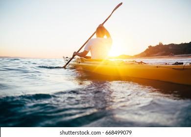 Man paddling the kayak at sunset sea. Kayaking, canoeing, paddling concept