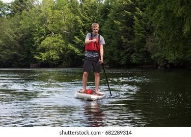 Man paddling on a stand up paddle board, Muskoka, Ontario, Canada.