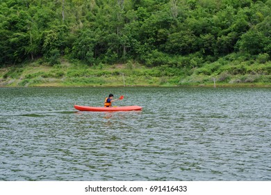 Man paddling in a red kayak boat in Thailand