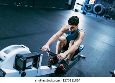 Man paddling and rowing on gym machine training alone