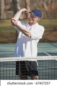 Man in pain with elbow sports inquiry on tennis court